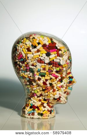 a head made of glass filled with many tablets. photo icon for drugs, abuse and addiction tablets. poster