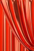 Red theater curtain with gathers under the lights fragment close-up view poster
