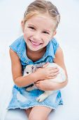 smiling little girl in denim clothing playing with a rabbit poster