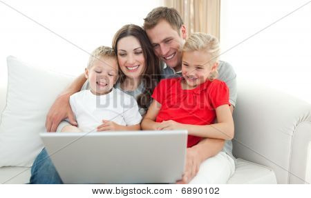 จอยฟูลครอบครัวที่ใช้คอมพิวเตอร์ที่นั่งอยู่บนโซฟา
