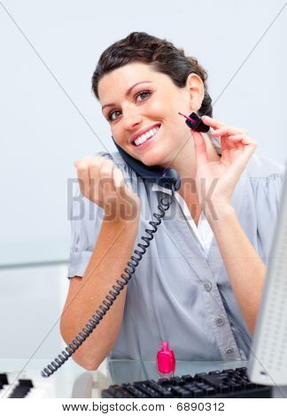 Attractive Business Woman On Phone Painting Her Nails