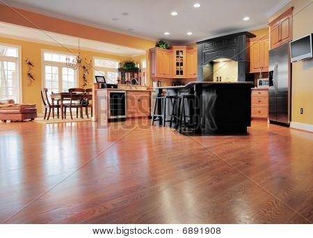 Home interior shows a large expanse of wood flooring in the foreground and a kitchen and dining room in the background. Horizontal format. poster