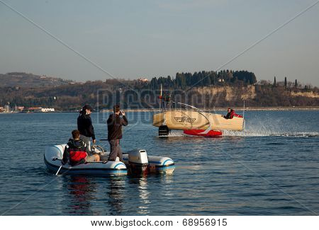 Portoroz, Slovenia - 6 May, 2014: Men riding a motorised vessel on foils in the sea and other men watching him on a boat.