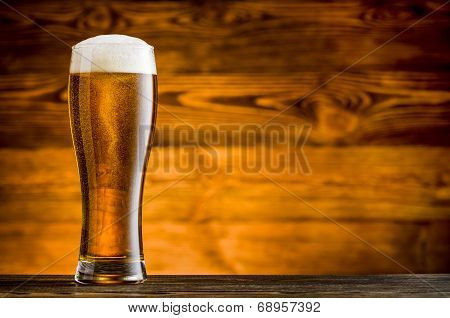Glass Of Beer On Wooden Table And Wooden Background