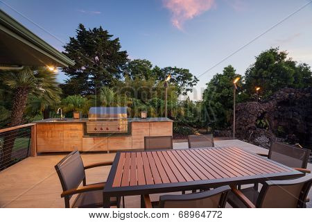 Backyard patio with BBQ grill and dining table on deck