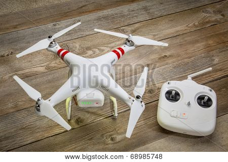 FORT COLLINS, CO, USA, JULY 24, 2014:  Radio controlled DJI Phantom quadcopter drone on a wooden deck with a flight controler ready to take off