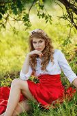 Romantic portrait of the woman in red skirt sitting under the tree poster