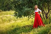 Romantic portrait of the woman wearing red skirt standing under the tree poster