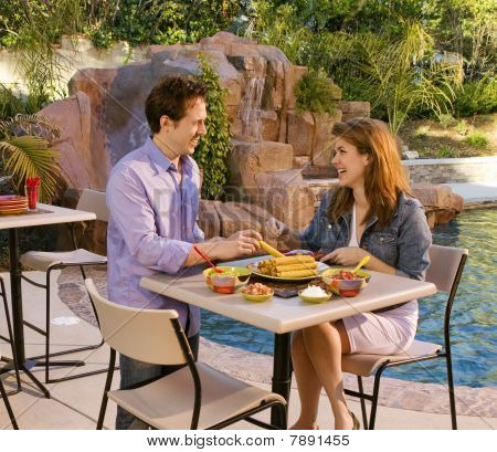 Couple by poolside eating