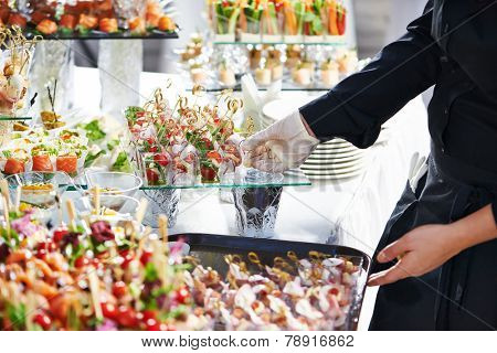 Waiter with meat dish serving catering table with food snacks poster