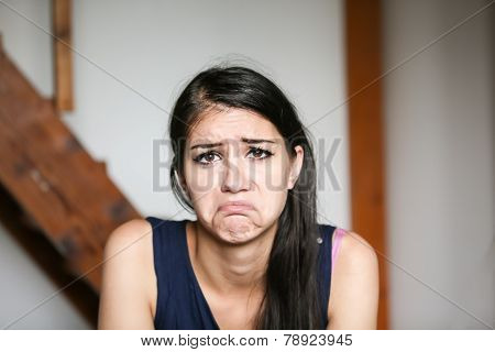 Beautiful brunette young woman with sad face. Sad expression, sad emotion, despair, sadness