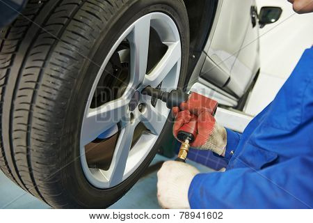 car mechanic screwing or unscrewing car wheel of lifted automobile at repair service station poster
