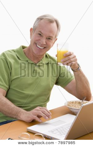 Man Using Laptop and Eating Breakfast