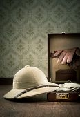 Explorer packing with open leather briefcase pith hat leather gloves on wooden surface. poster