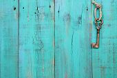 Brass skeleton key hanging by rope on antique teal blue shabby wood background poster