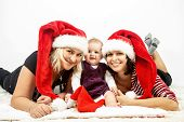 smiling infant baby with mother and her aunt with santa hats poster