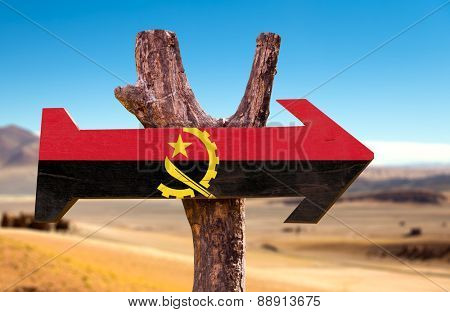 Angola Flag wooden sign with desertic road background