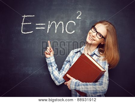 Happy Student Girl With Book And Glasses Has Written On  Blackboard Formula