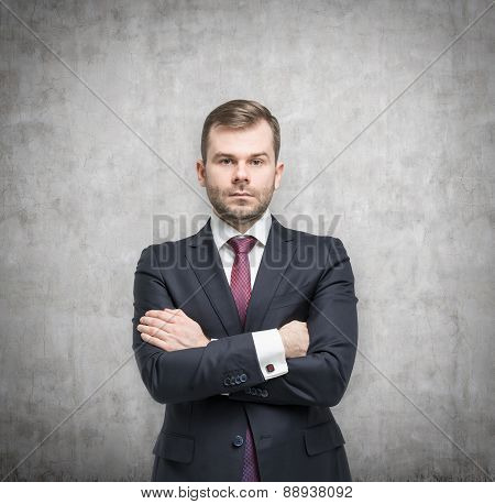 Young Handsome Businessman In A Suit Is Standing In A Concrete Room