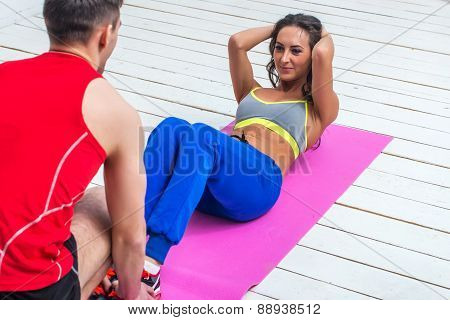 athletic sporty couple friends. Woman doing crunches abdominal exercises on floor in gym with a help