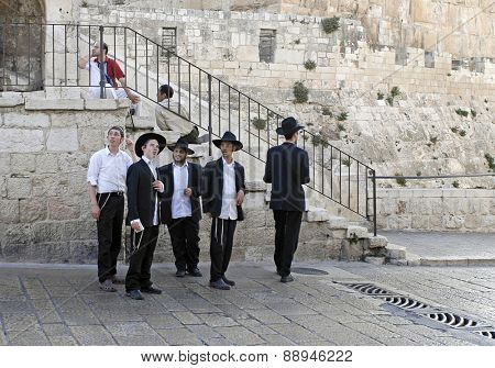Jerusalem, Israel - June 8, 2007: Young Jewish men stand at Jaffa Gate, one of eight gates to the Old City, while staring in awe at the early 16th century walls of the Holy Land of Israel.