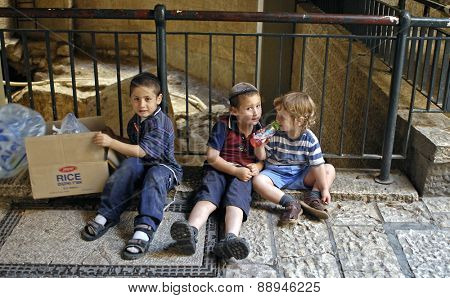 JERUSALEM, ISRAEL-JUNE 11, 2007: Three Jewish boys play innocently, without supervision, in streets of ancient Roman Cardo, now part of a shopping arcade in the Jewish Quarter of Old City, Jerusalem.