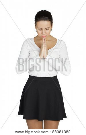 Young woman standing for white background with her hands folded and eyes closed, praying.
