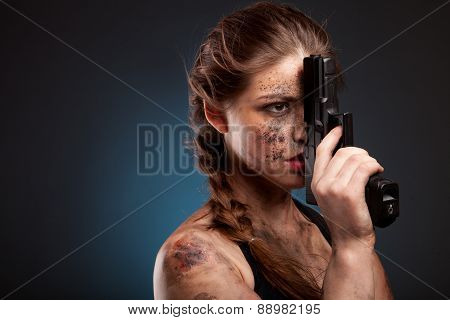Sexy girl in a black dress holding a gun. Amazon girl. With blood on face. On dark background.