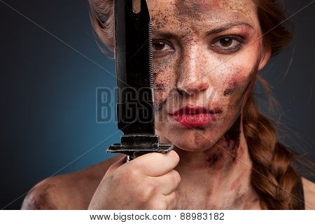 Portrait of a young sexy girl with a knife in his hand. With blood on face. Killer woman