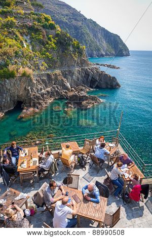 RIOMAGGIORE, ITALY - APRIL 12, 2015: People sitting at the sea in Riomaggiore village, Italy. Riomaggiore is one of five famous coastline villages in the Cinque Terre National Park, Liguria.