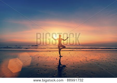 Silhouette of woman meditating on the sea beach. Yoga and fitness.