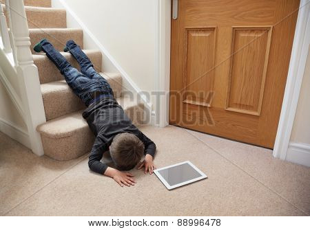 Child falling down the stairs whilst playing on digital tablet not concentrating concept for safety at home poster