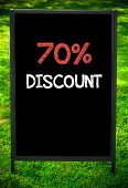 SEVENTY PERCENT DISCOUNT message on sidewalk blackboard sign against green grass background. Copy Space available. Concept image poster