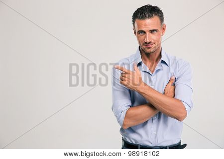 Happy businessman pointing finger away over gray background. Looking at camera
