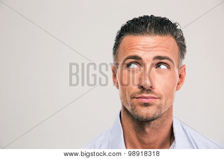 Closeup portrait of a handsome man looking away at copyspace over gray background