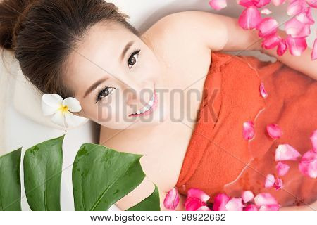 Beautiful Asian beauty woman in bath with rose petal. body care and Spa