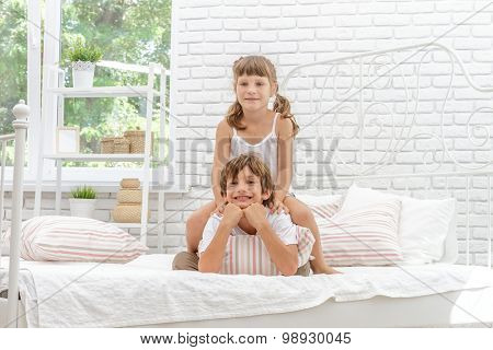 indoor portrait of young happy smiing children, girls and boy, in bed, happy morning time