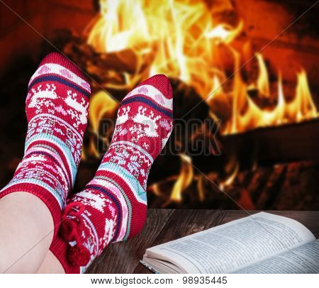 Christmas Female Legs In Socks On The Background Of A Burning Fireplace