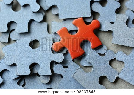 Orange puzzle pice standing above the rest of puzzle pieces. Conceptual photograph to display business personal financial success or a leadership concept.