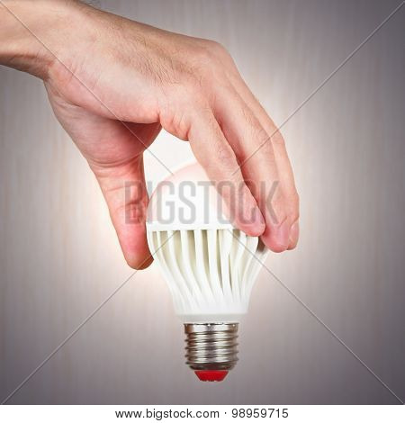 Hand holding a glowing ecofriendly bulb on light wood background