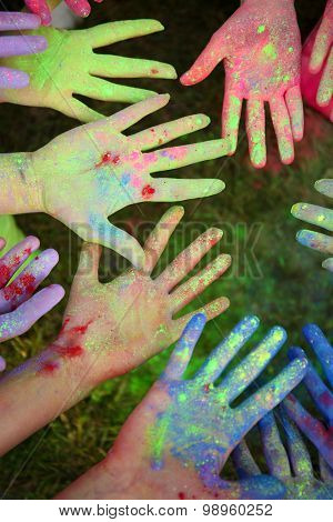 Hands of young people with Indian dyes on Holi color festival poster