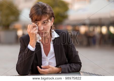 Tearful Woman Sitting Outdoors Crying