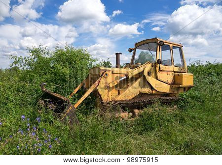 An old, abandoned bulldozer was parked in the grounds and is now rusted and overgrown with plants poster