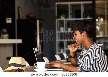 Smiling Young African American Woman Working On Laptop