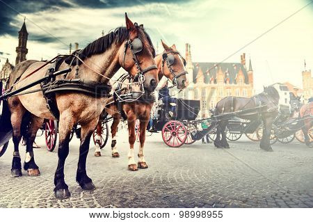 Horse-drawn Carriages On The Old Market Square. Bruges, Belgium