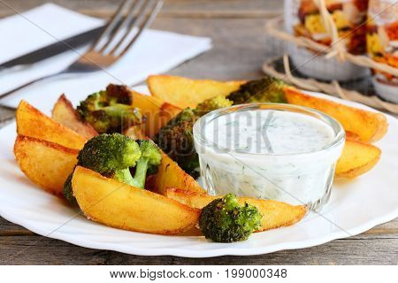 Homemade baked potatoes and broccoli with sauce on a plate and a wooden table. Easy baked potatoes and broccoli recipe. Delicious vegetarian lunch or dinner. Closeup