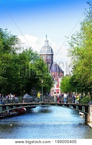 Amsterdam Netherlands - July 12 2017: Pedestrians walking in Amsterdam known for its artistic heritage numerous canal system and narrow houses with gabled facades.