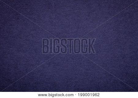 Texture of old navy blue paper background closeup. Structure of dense dark denim kraft cardboard.