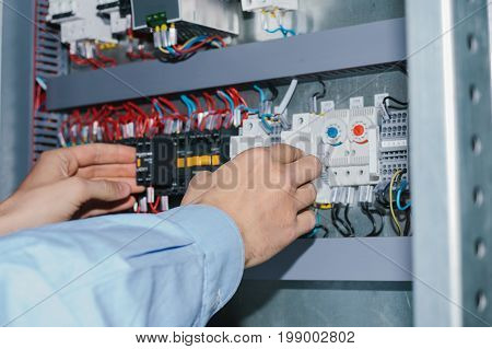 Photo of male electrical technician specialist checking indoor electric low-voltage cabinet equipment