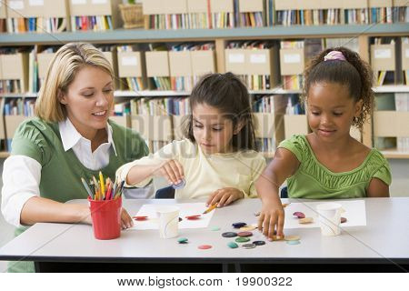 Two students in art class with teacher